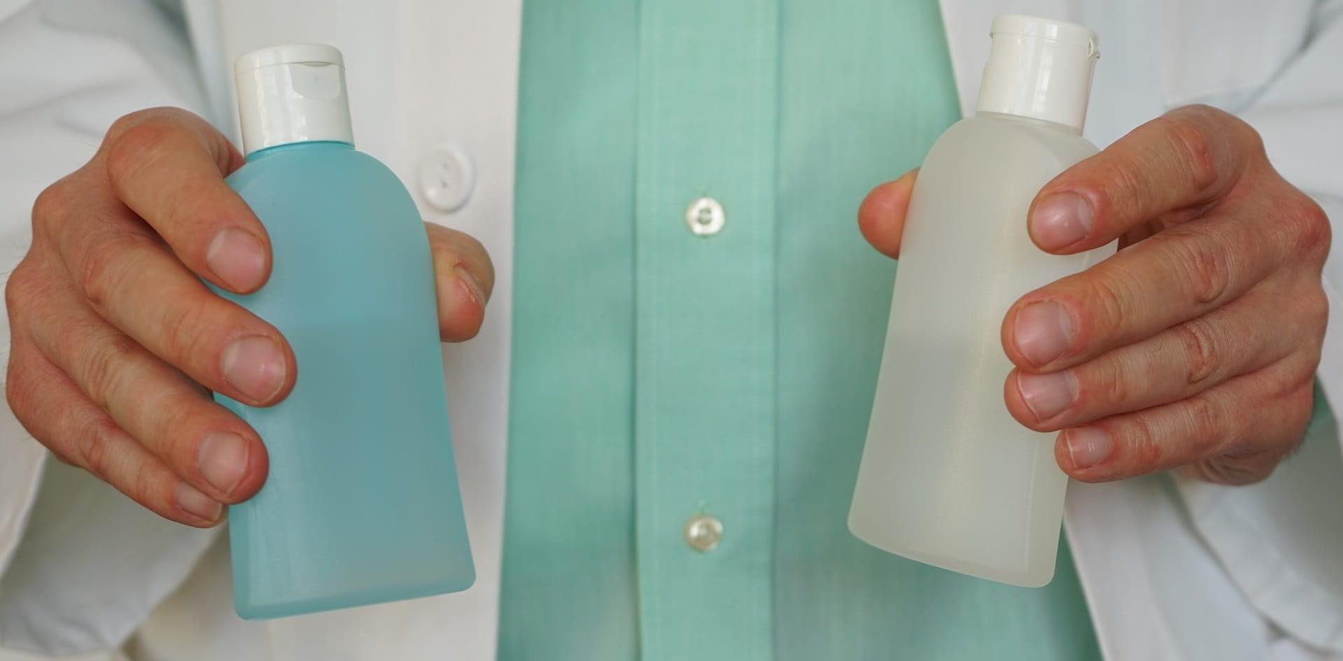 Arzt zeigt zwei Flaschen Handdesinfektion
